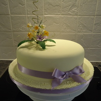 Easter/spring Cake For A Cancer Charity Raffle This is a 10x8 inch oval fruit cake, iced with lemon fondant and lilac ribbon accents. The flower arrangement is a mixture of tiny...