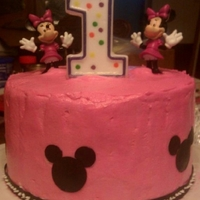 Minnie Mouse First Birthday yellow cake with pink and white icing. ears are plastic and can be use later. decorations are sugar sheets