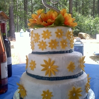 Daisies And Sunflowers White cakes and white buttercreams icing with yellow fondant daisies with silk sunflowers on top with blue buttercream trim to match the...