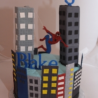 Spiderman Iced in buttercream, and all other decorations are gumpaste. Spiderman is swinging between buildings by strings.