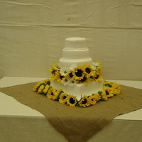 Sunflower Wedding 4 tier wedding cake.pound cake, devil's food chocolate, white velvet and red velvet. Covered in Butter Cream and fondant. Flowers are...