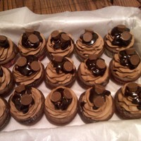 Peanut Butter Cup Cupcakes   Dark Chocolate cake with a Reeses Peanut Butter Cup baked inside. Topped with Chocolate buttercream, ganache and mini reeses pb cups.