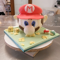 Mario! 3D Sculpted Mario cake for class. Nose in the picture is still being supported by a piece of foam.