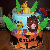The Lion King  Birthday cake with Lion King theme. Characters are fondant, flowers and leaves are gumpaste. Bottom tier is frosted with yellow orange...