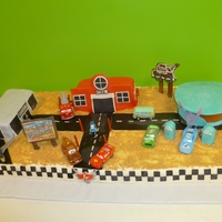 "Cars 2 Cake ""Cars 2"" themed cake for a 4 year old. ""Sand"" is crushed graham cracker. Vehicles are real toys borrowed from the..."