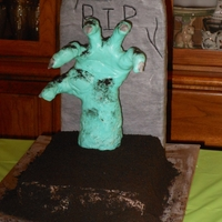 Zombie The hand was made from sculpted rice crispy treat and covered with fondant. The head stone was a styrofoam board covered with marbled...