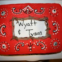 "Cowboy Cake/boots Red/Black swirled white cake, buttercream icing, fondant ""bobwire and boots"". Used the themed napkins for pattern/colors."