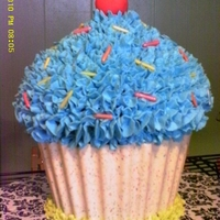 Giant Cupcake Made using chocolate shell for cupcake liner. Sprinkles and cherry are fondant/gum paste mix.