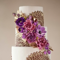 Purple & Gold Wedding Cake  Purple starburst lace molds brushed with gold & an arrangement of sugar flowers with gold leaves & ribbon (photo by Mark Davidson...