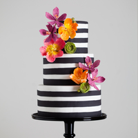 Black And White Stripes With Bright Sugar Flowers Black and white fondant stripes, done with a hand-cut strips kind of look in mind. The brightly colored sugar flowers include poppies,...