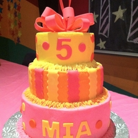 Polka Dots & Stripes 3 tier cake iced in pink, yellow, & orange buttercream with fondant stripes & polka dots and bow topper.