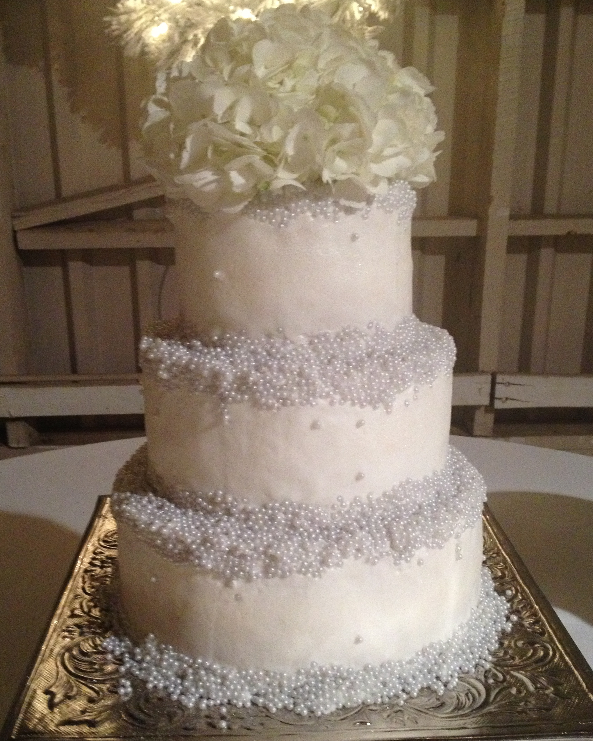 Round, Pearl Encrusted Wedding Cake buttercream fostingsugar pearl accentshydrangeas on top