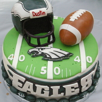 "Philadelphia Eagles Birthday Cake 10"" yellow cake with buttercream filling covered with MMF. Helmet and and football made of RKT and covered in MMF. All accents MMF...."