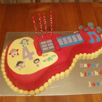 Wiggles Guitar Cake this cake is based on my son's favourite toy its a white choc mud coloured in wiggles colours, ganached then covered in fondant &...