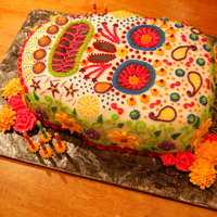 Day Of The Dead Cake This is a white cake with caramel buttercream icing. Flowers are royal icing and gems are sugar.