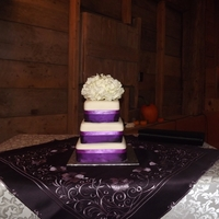 Hydrangea Wedding Cake Three tier, square, vanilla cake with Italian meringue buttercream, covered in ivory mmf. Purple ribbon and real hydrangea on top.