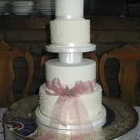 Pink Fantasy Wedding Cake   Four tiers covered in fondant with fondant flowers.