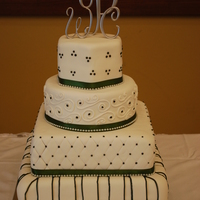 Harrel Wedding Cake Four tier wedding cake, all four tiers covered in white Satin Ice fondant with forest green accents.