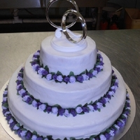 Lavender/purple Rose Wedding Cake  This is the first wedding cake I have ever made. The icing isn't perfect but everyone loved and and said it tasted great! This cake is...