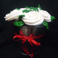 White Rose Bucket Chocolate cupcakes with white buttercream...rose bouqet in a silver bucket. Wife got them for her hubby for valentines day :)
