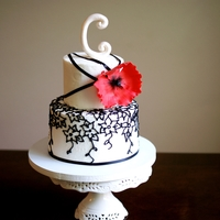 2 Anniversary Cake Client designed cake. buttercream with black piping and a red poppy. Black ribbon and a gumpaste C.