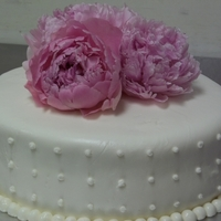 Peonie Wedding Cake Marshmallow fondant, royal icing dots, pink peonies, on layered red velvet cake. Buttercream crumb coat and filling.