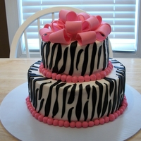 Pink Zebra Cake White cake with white buttercream. Zebra stripes and pink balls are fondant, and the bow is a mix of fondant and gumpaste.