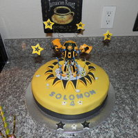 Bumble Bee Transformer Cake Marble Cake, 12 inch round. MMF covering cake, trim, stars and letters. The Transformer is a toy sitting chocolate rocks.