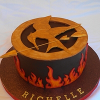 Hunger Games Cake Cake covered in chocolate ganache, mocking jay is gumpaste painted with gold, flames are hand-painted fondant.