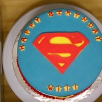 Superman Cake  Cake is covered in MMF and decorations made with regular fondant and butter cream. Cupcakes are vanilla BC and decorations are painted...