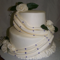 Wedding Cake Two tiered cake in buttercream fondont roses and swag