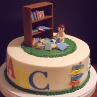 Loving The Books   Buttercream base, candy clay accessories, fondant bookshelf, Sculpey clay figure