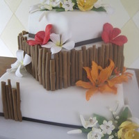 Tropical Flower Wedding Cake Square off set three tier cake with gum paste flowers and fondant bamboo.