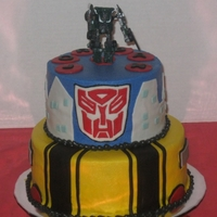 Transformers White and chocolate cake covered in buttercream, fondant details, toy transformer.