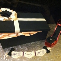 Shoebox And Stiletto Cake Shoebox cake with gumpaste bow, flower, and heal.
