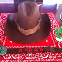 Cowboy Birthday Brim of hat is made out of chocolate fondant/gumpaste mixture. Cake is covered in fondant and hat band is fondant as well.