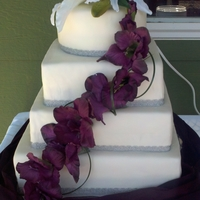 Square And Round Wedding Cake With White And Purple Orchids Four tier wedding cake, top tier 8 inch round, other tiers square (10, 12, 14 inch). All white with buttercream filling. Iced with...