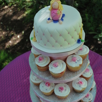 "Fairy Cake/cupcakes  6"" cake on top with sculpted fondant princess fairy to match invitations. Ribbon roses and a crowns are placed on the sides. The..."