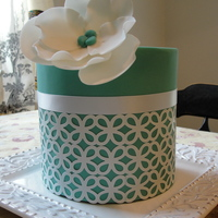 Teal Cake The design was made by punching edible paper with a craft punch, the ribbon is real, and the flower is gumpaste. The cake is a 6-inch cake...