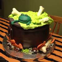 Cauldron Cake Cauldron Cake, Half chocolate and half red velvet covered in fondant. Fondant frog; white chocolate bones and flames, and candy rocks.