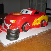3D Lightning Mcqueen Cake I made this cake for my friends son's 3rd birthday. I carved the cake into the shape of lightning mcqueen and then covered it in MMF...