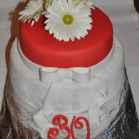 30Th Birthday Cake  2 tier chocolate cake with chocolate SMBC covered with ganache and fondant.Birthday girl loves red and gerberas and this was a surprise...