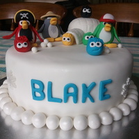 Blake's Club Penguin Raindow Cake  My son loves Club Penguin, so this is his 10th birthday cake. Just a plain vanilla cake made into rainbow colors, covered in white...