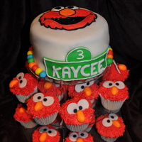 Elmo! The cake is chocolate cake filled with chocolate ganache. The Elmo is buttercream. The cupcakes are vanilla cupcakes topped with...