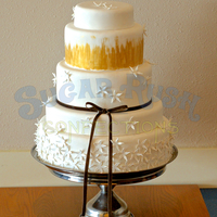 White Flowers And Gold Wedding Cake White fondant with white gum paste flowers, edible gold painting