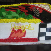 Lightening Mcqueen Cake yellow cake filled with half chocolate fudge and half venetian cream with fresh strawberries. Covered in BC and fondant accents