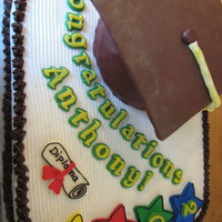 Graduation Cake Buttercream icing, with fondant decorations. Letters are tinted chocolate.