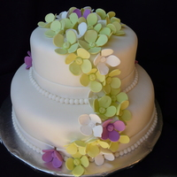 "Hydrangea Wedding Cake 12"" tier chocolate cake filled with strawberry filling, 8"" tier of lemon filled with raspberry filling. Covered in buttercream..."