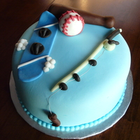 "Sporty Cake 9"" round torted with buttercream and then covered with MMF. The person liked baseball, snowboarding and fishing. Difficult combination..."