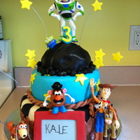 "Toy Story 3 Cake Three tier cake (Bottom is 10 inch, middle is 8 inch and top is half of ball cake). Covered in fondant with fondant accents. ""Etch-a-..."